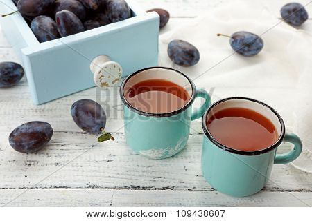Plum Juice in mugs with fresh fruits