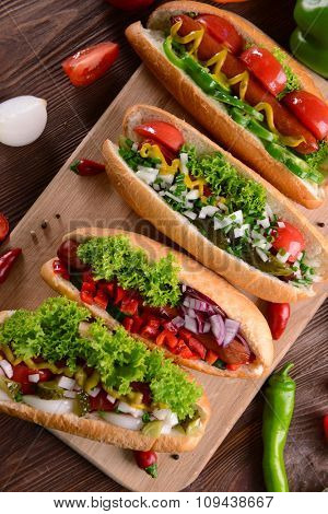Hot dogs and vegetables on wooden cutting board