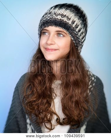 Portrait of nice stylish teen model wearing warm hat and posing over blue background, dreamy looking in side, winter fashion for girls