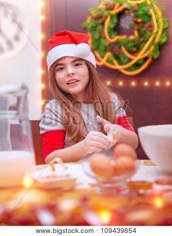 Portrait of cute baby girl cooking for Christmas, little Santa helper, baking something sweet, traditional preparation to holidays