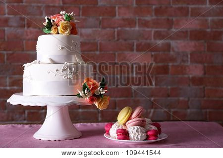 Beautiful wedding cake decorated with flowers and plate with cakes on pink table against brick wall background