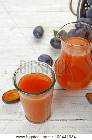 Plum Juice in jar and glass with fresh fruits