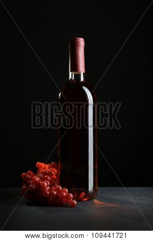 A bottle of wine and red grapes, on grey-black background