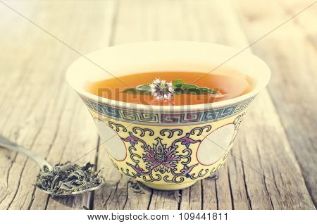 Cup of tea with a flower, fresh mint and dry tea. Asian culture. Alternative medicine. Herbal