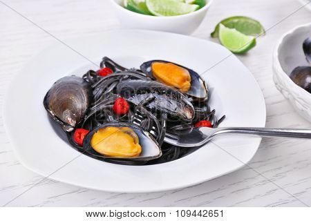 Cooked pasta, mussel and lime on white wooden background