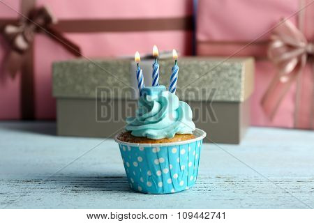 Sweet cupcake with candle on blue wooden table against pink present boxes