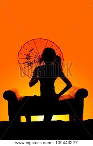 Silhouette Of Woman Sit With Umbrella Behind Head