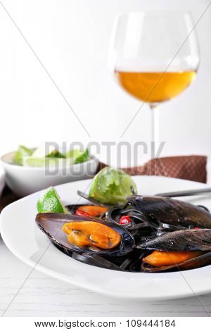 Cooked pasta, mussel, lime and wine on the table, close-up