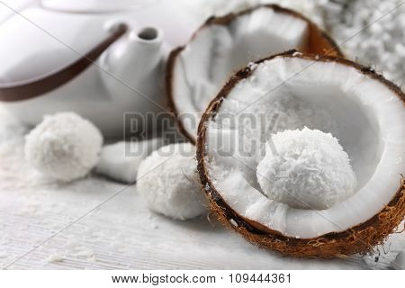 Candies in coconut flakes and fresh coconut on  light wooden background