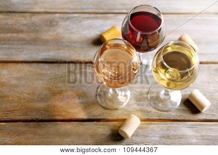Crystal wine glasses and corks on wooden background