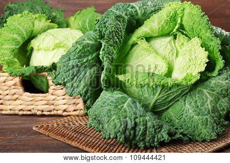 Savoy cabbage in wicker basket on wooden background