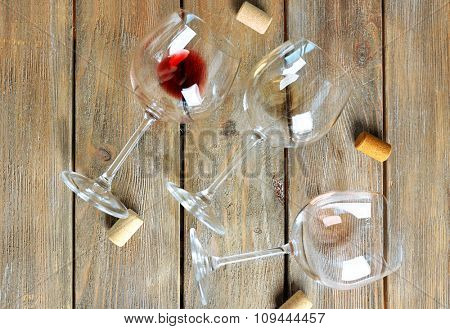 Empty wine glasses and corks on wooden background