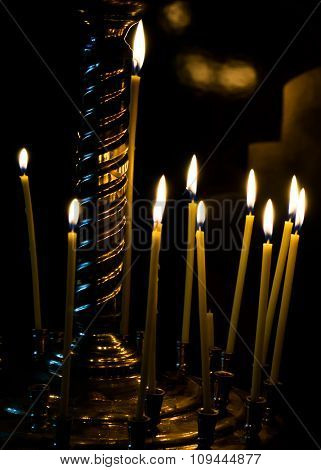 Burning Candles On Gold Candlestick In The Church Isolated On Black Background