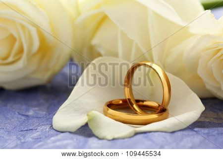 Golden Wedding Rings On A Purple Paper Background