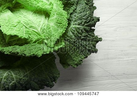 Savoy cabbage on light wooden background, close up