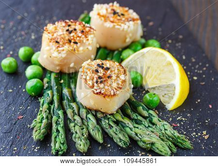 Fried Scallops With Sesame Seeds, Asparagus, Lemon And Green Peas On A Black Plate