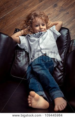 Little Boy Lying On Brown Leather Chair