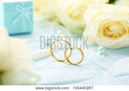 Golden Wedding Rings On A Blue Wooden Table