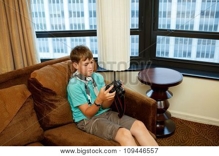 boy sitting on the couch with a camera in hand