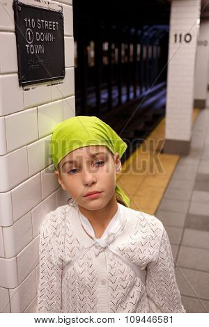 sad girl stands leaning against a column in the New York subway