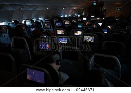 passengers watch movies in a dark aircraft cabin