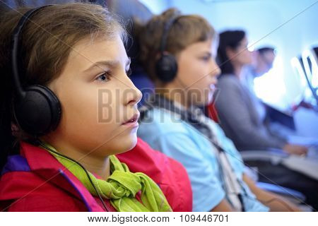 girl and boy with headphones on an airplane