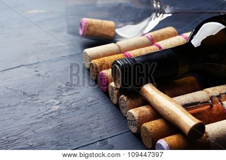 Bottle of wine and corks on wooden table