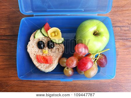 Lunch box with creative sandwich and fruits on wooden background