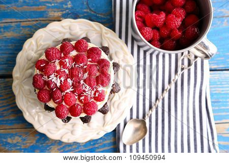 Sweet cake with raspberries on wooden table background