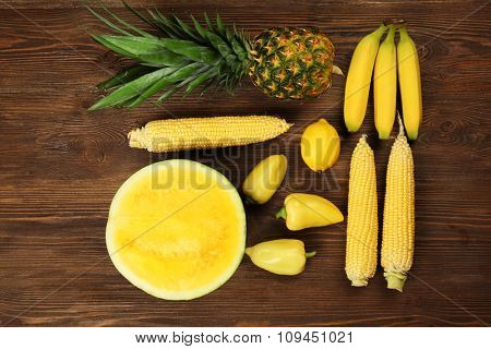 Yellow composition of fruit and vegetables on wooden background