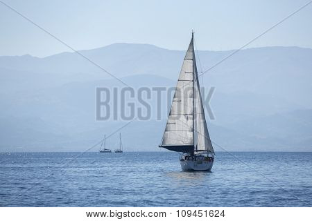 Sailing in the wind through the waves early in the morning. Luxury yachts.