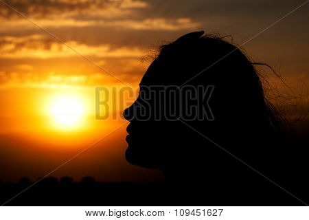 Young Girl Face Silhouette Looking On Beautiful Cloudy Sky With Orange Sunset
