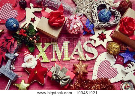 high-angle shot of some letters forming the word xmas on a red rustic wooden surface surrounded by a pile of gifts and different cozy christmas ornaments