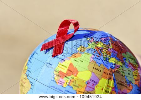 closeup a world globe with a red ribbon for the fight against AIDS