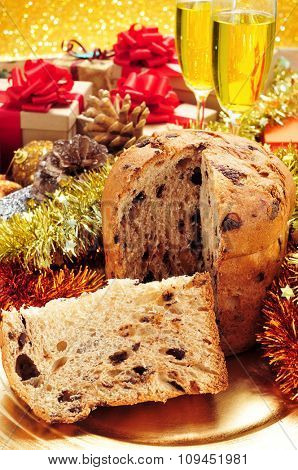 closeup of a panettone, a typical Italian sweet for Christmas time, on a set table with some glasses with champagne and some gifts in the background