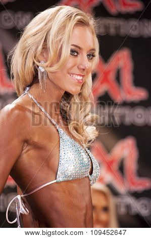 Blond Female Bodyfitness Model Smiles To The Crowd