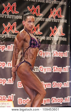 Female Bodybuilder In Triceps Pose And Purple Bikini