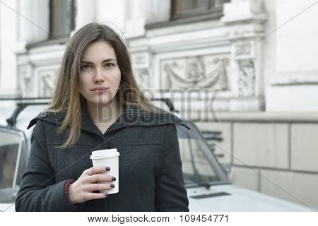 Young woman drinking coffee outdoor, image toned.