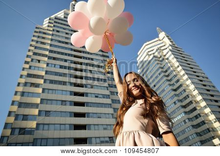 Beautiful young girl holding colored balloons over high-rise building. Urban teenage background.