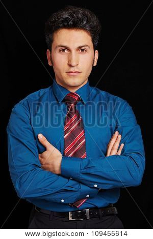 Serious looking businessman with his arms crossed on a black background