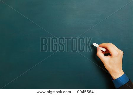 Business man holding hand with chalk on empty green chalkboard