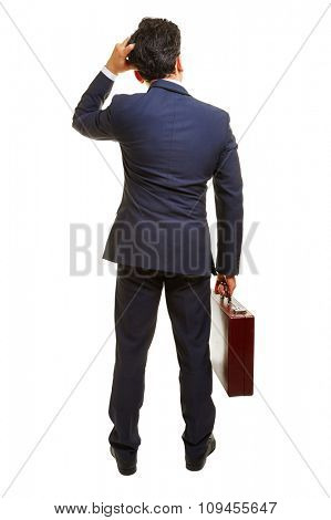 Pensive business manager from behind with briefcase in his hand