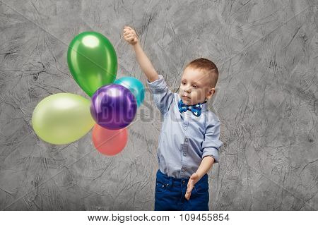 Portrait of a cute little boy in jeans blue shirt and bow tie with multi-colored balloons in hands on a gray textural background in studio