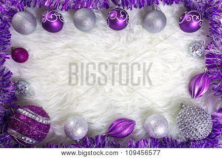 Frame made by purple and silver christmas baubles on fluffy carpet