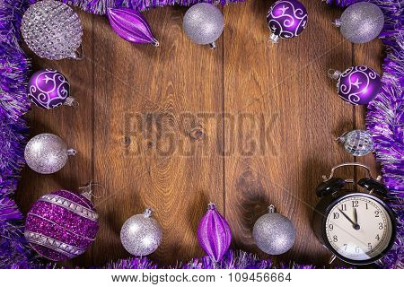 Frame made by purple and silver christmas baubles and clock on wooden floor