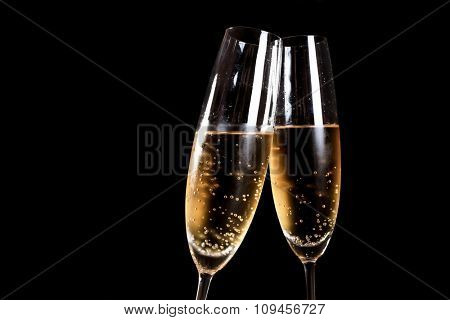 Two flutes of champagne on black background