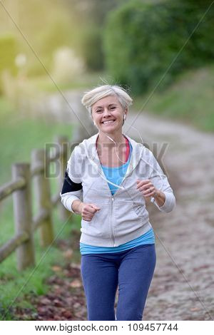 Senior woman jogging outside with earphones on