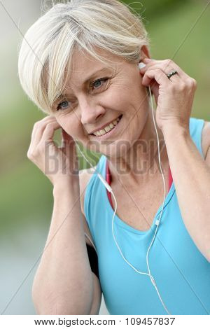 Portrait of senior woman adjusting earphones before exercising