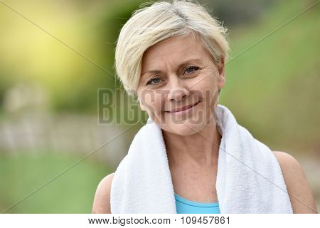 Portrait of athletic senior woman with towel around neck