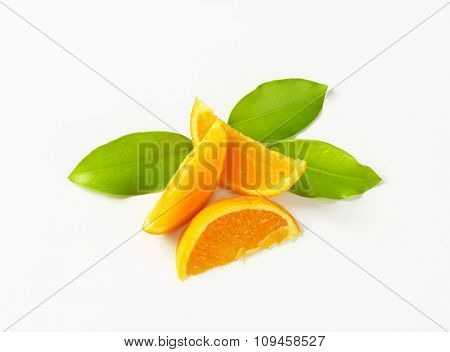 three slices of fresh orange with leaves on white background